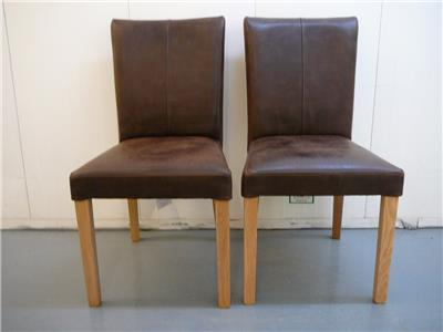 pair of calia dining chairs in distressed leather and oak