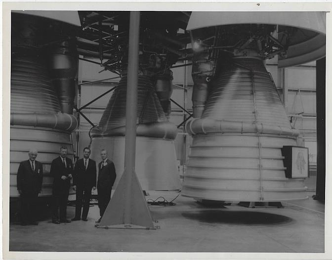 ORIGINAL PHOTOGRAPH OF GROUP OF MEN STANDING IN FRONT OF SATURN ENGINE, MARSHALL SPACE FLIGHT CENTER, Photograph
