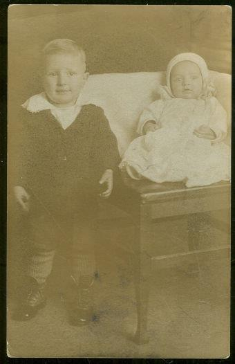 Image for REAL PHOTO POSTCARD OF LITTLE BOY STANDING NEXT TO BABY