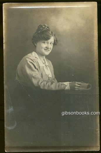 REAL PHOTO POSTCARD OF MADGE SITTING AT A TABLE, Postcard