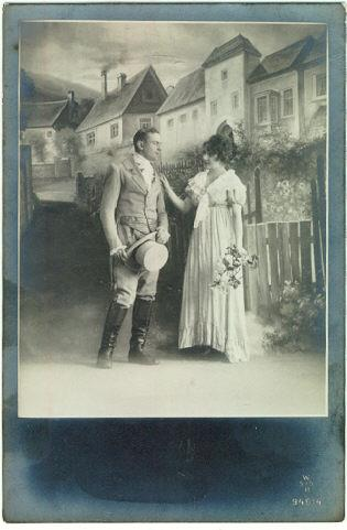 PHOTO POSTCARD OF ROMANTIC COUPLE DRESSED UP IN FRONT OF A PAINTED SET, Postcard