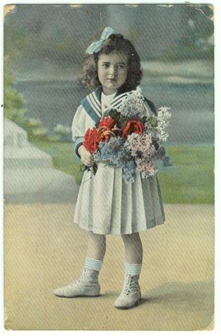 Image for LITTLE GIRL DRESSED UP IN A SAILOR OUTFIT HOLDING A LARGE BOUQUET OF FLOWERS