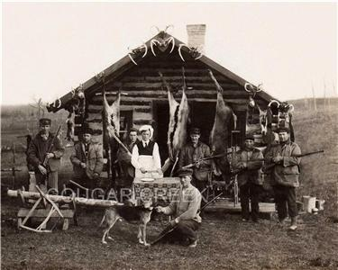 Photo Of Seven Hunters And The Cook With Three Whitetail Deer And Rabbits  Hanging From The Front Porch Of Their Log Hunting Cabin.